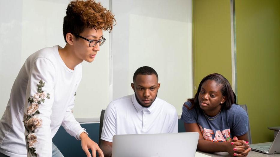 three students sitting at a desk